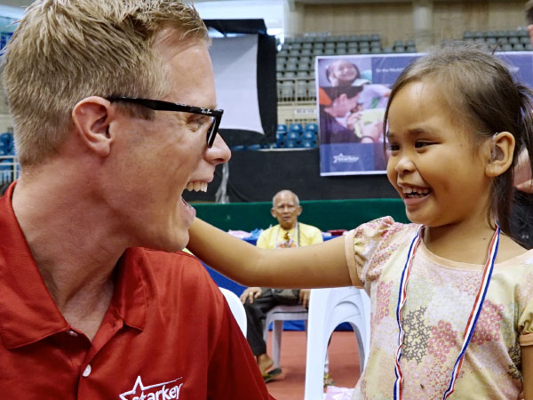 A Spotify employee volunteering with Starkey smiles with a girl he just fitted for a hearing aid.