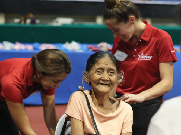 Spotify volunteers and Starkey employees work together to fit an older woman with her first hearing aid.